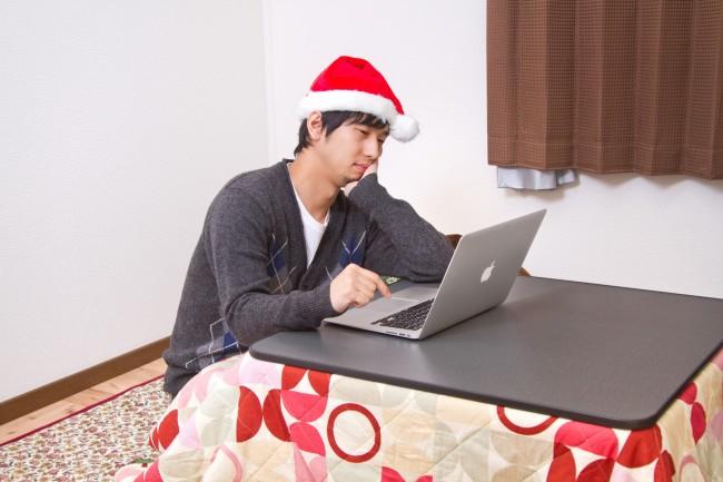 サンタ帽を被ってノートパソコンを触る男性