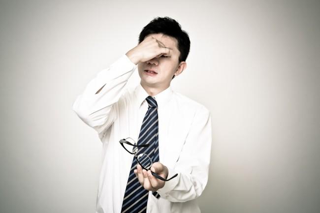 眼精疲労のスーツ姿の男性