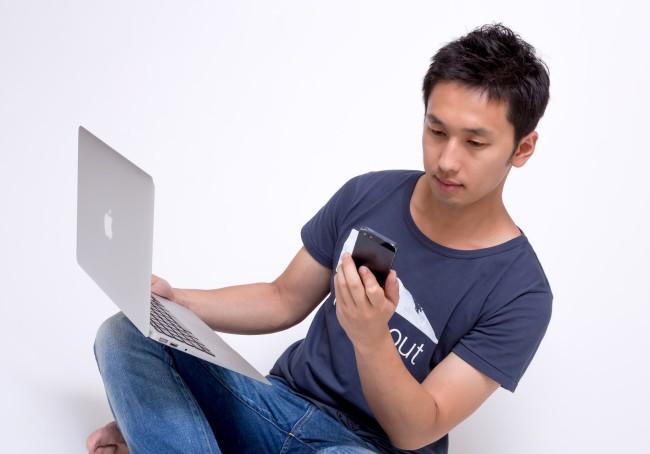 ブラウザとMacBookを使う男性