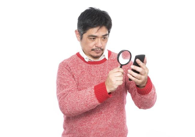 虫眼鏡でスマートフォンを見る男性