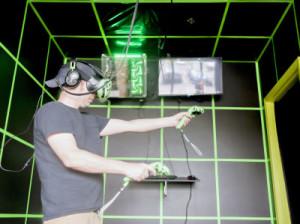 VRアーケードの個室でゲームをする男性